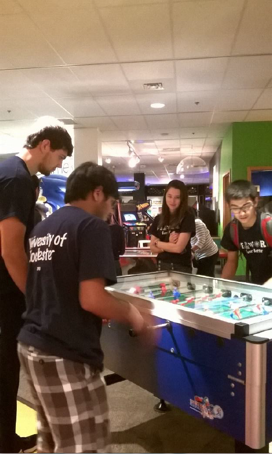 Counselors and students participate in a friendly game of foosball
