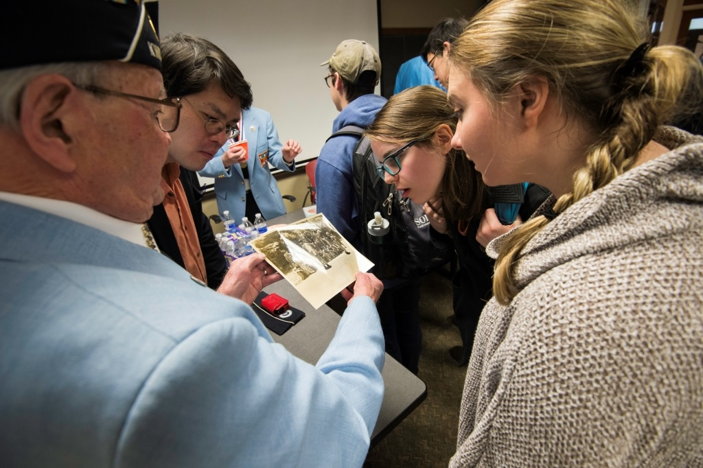 Roger Hill, Rochester KWVA chapter commander, shows a photo of captured North Korean soldiers to professor Daphon Ho and students Maureen Lamont '16, and Christina Rutherford '16.