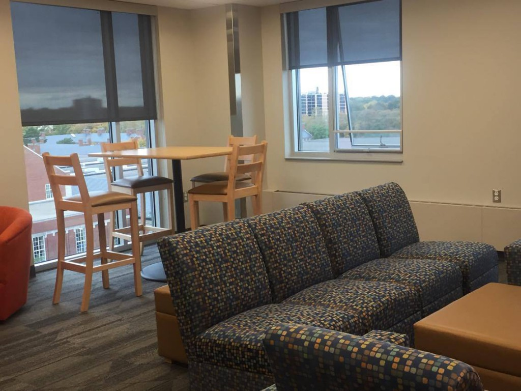 Lounge with couch, bar table and chairs, windows with a view of campus