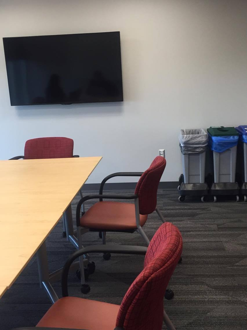 Study room with a wall-mounted TV, long table, chairs