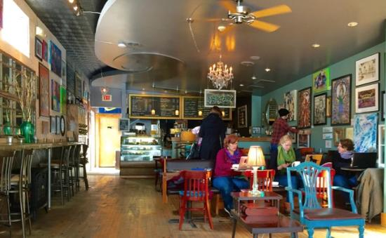 A colorful coffee shop with art on the walls and people lounging and drinking coffee