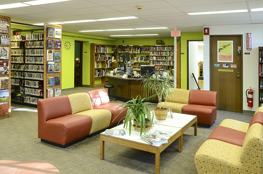 Art & Music Library with shelves of DVDs, plants, cozy couches, magazines, art, and lime green walls