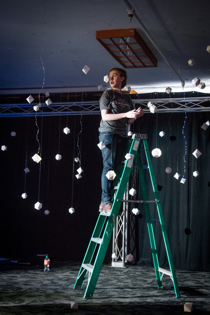 One of the students on a ladder installing hanging paper art on the ceiling