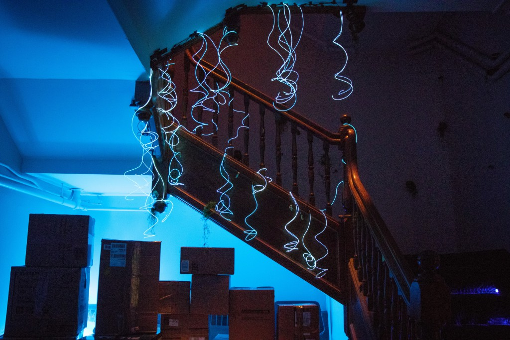 glowing wires hang over a staircase and a series of boxes