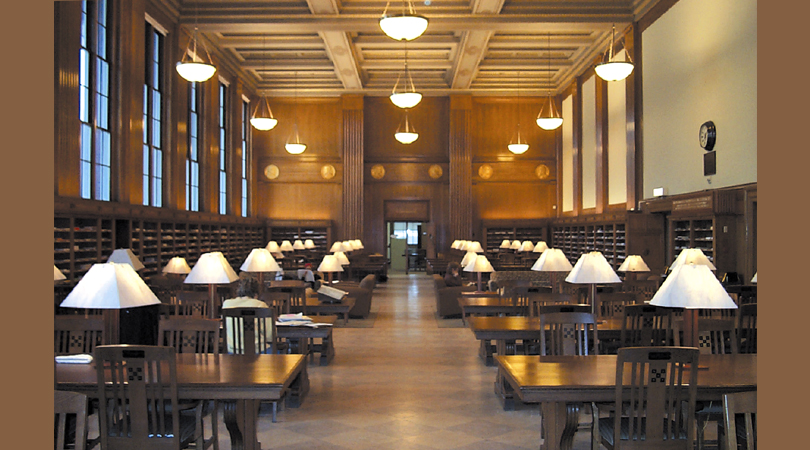 The Perodical Reading Room with long wooden tables, rows of bookshelves, elegant paneling, and table and ceiling lamps