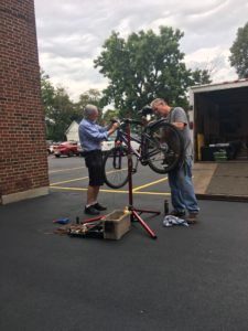 Two men fixing a bicycle