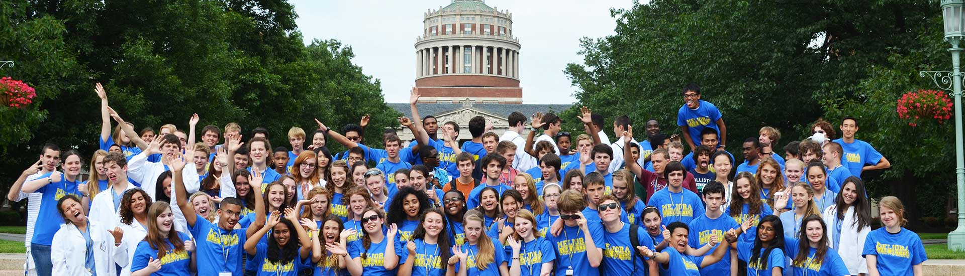 A large group of Pre-College students pose in front of Rush Rhees Library
