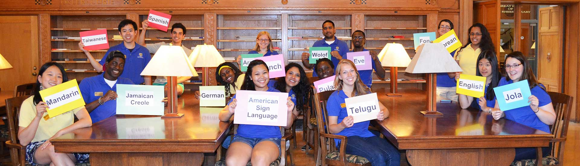 Students pose with signs of different languages