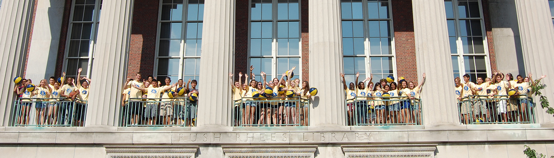 Students pose on the balcony of Rush Rhees Library