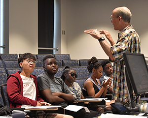 Students listen to a teacher lecturing