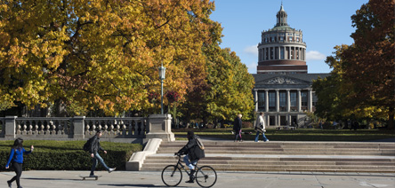 Student biking in front of Rush Rhees Library