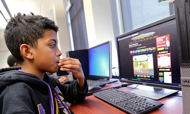 A young student looking at a computer screen